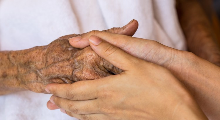 elderly person's hand clasped in young person's hands