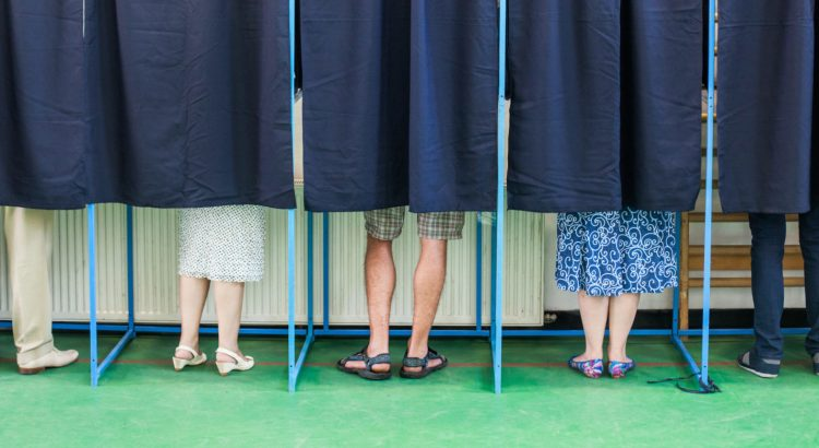 image showing a line of voting booths, with legs showing