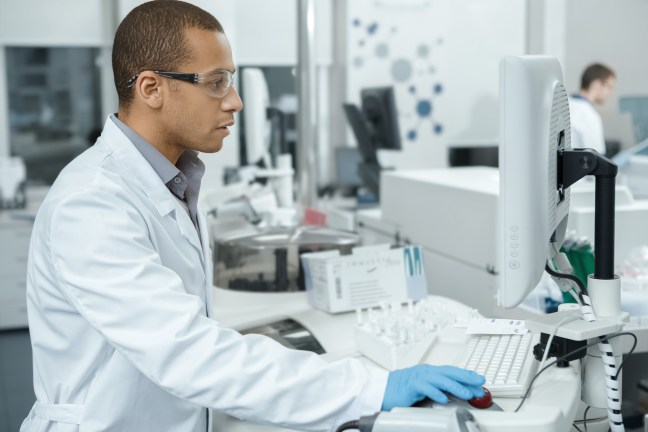 researcher in a lab looking through microscope