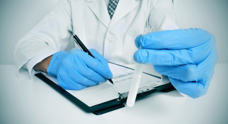 doctor wearing gloves holding sperm sample in test tube while writing on clipboard