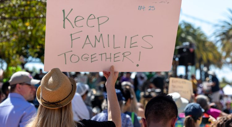 "Protestor holding up a sign that reads ""Keep families together!"""