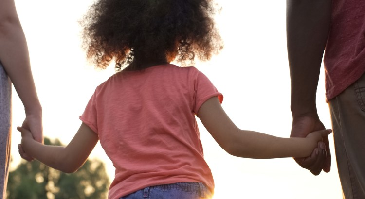 child pictured from the back holding both parents' hands.