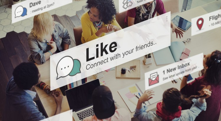 Social media concept: students sit at a table with social media notification bubbles floating above them.