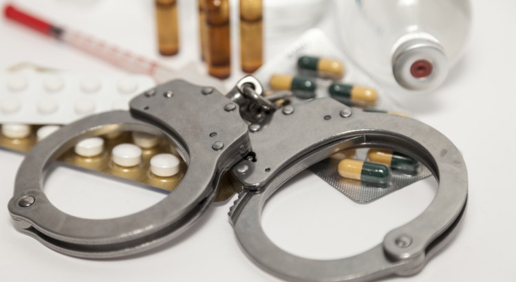 Handcuffs on a pile of pills