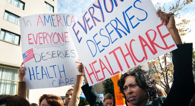 "Protesters hold up signs that read ""everyone deserves healthcare"""