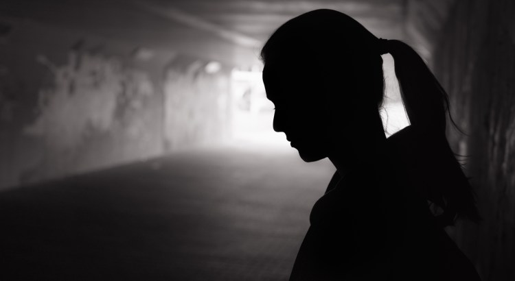 Black silhouette of girl with a pony tail looking down in a dark tunnel