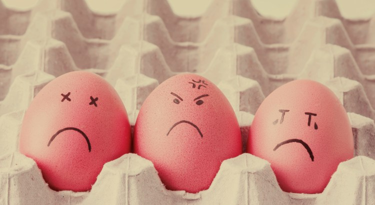 Three eggs in a carton with sad faces drawn on.
