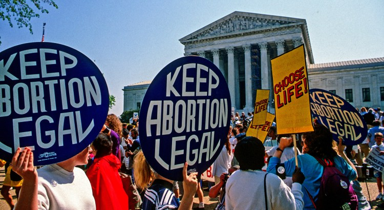 Pro-choice and pro-life protesters face off in front of the Supreme Court