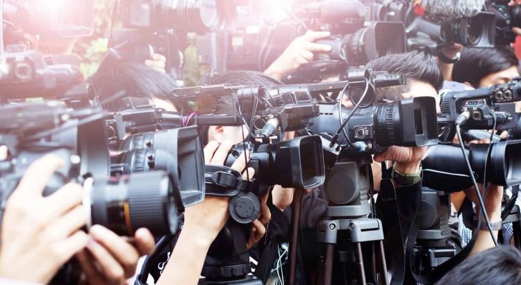 swarm of media and tv cameras
