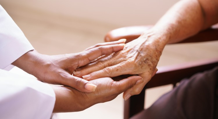 Hands of a young doctor wrapping around the hand of an elderly person