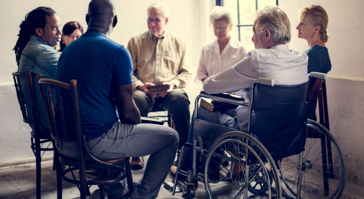 Group of people of various ages and ethnicities sitting in a circle talking. At least one of the people is in a wheelchair.