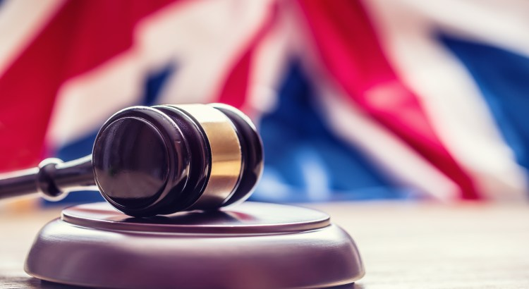 Photograph of a gavel in front of a British flag