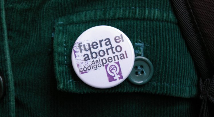 "Photograph of a button pinned to a shirt. The button reads ""Fuera el aborto de codigo penal."""