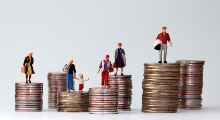 A photograph of miniature figures of people standing on top of piles of coins at different heights