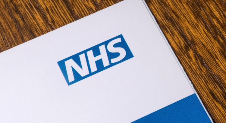 "Photograph of a report on a table, the report is labeled, ""NHS"""