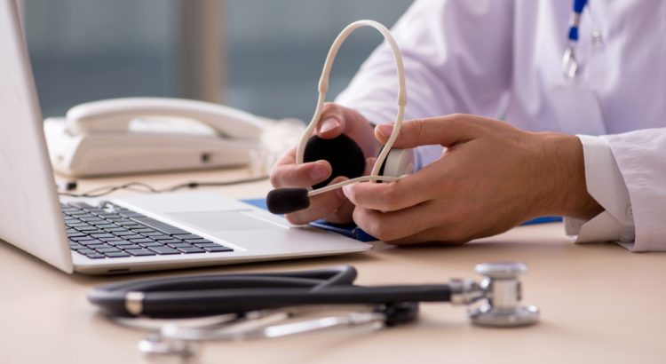 Photograph of a doctor holding a headset sitting in front of a laptop