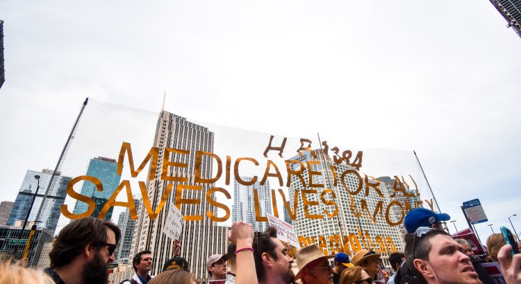"CHICAGO, ILLINOIS, USA - JUNE 8, 2019: First ever Medicare for All rally led by Bernie Sanders held in The Loop of Chicago. Crowd holds up a sign that says ""Medicare for All Saves Lives""."