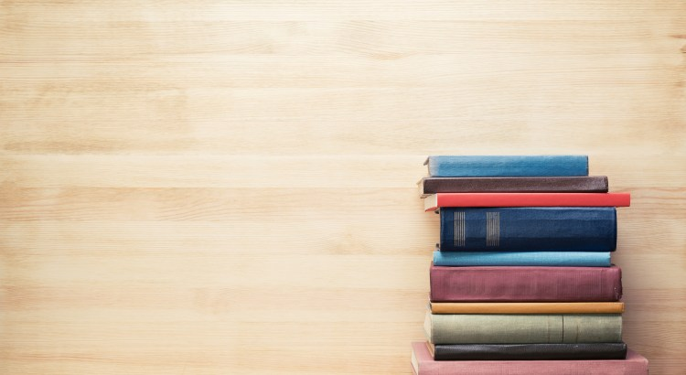 Stack of colorful books in front of a wood paneled wall
