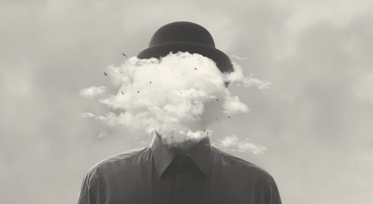 Surrealist black and white photograph of a person wearing a bowler hat and button down shirt. Ther person's face is obscured totally by a tiny cloud