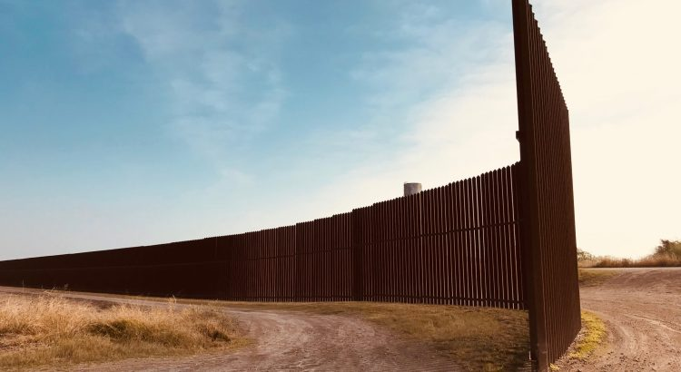 U.S.-Mexico border wall in Texas near a dirt road