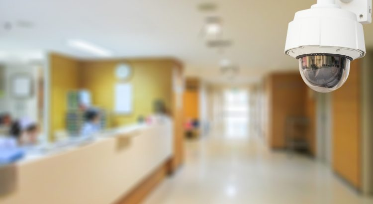A surveillance camera in focus in the foreground of hospital hallway.