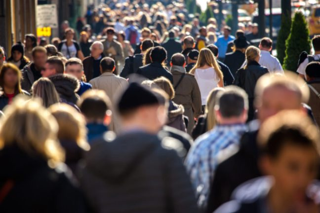 a crowd of people shuffling through a sidewalk