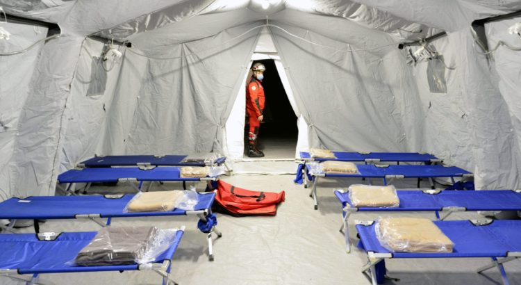 LOMBARDIA, ITALY - FEBRUARY 26, 2020: Empty hospital field tent for the first AID, a mobile medical unit of red cross for patient with Corona Virus. Camp room for people infected with an epidemic.