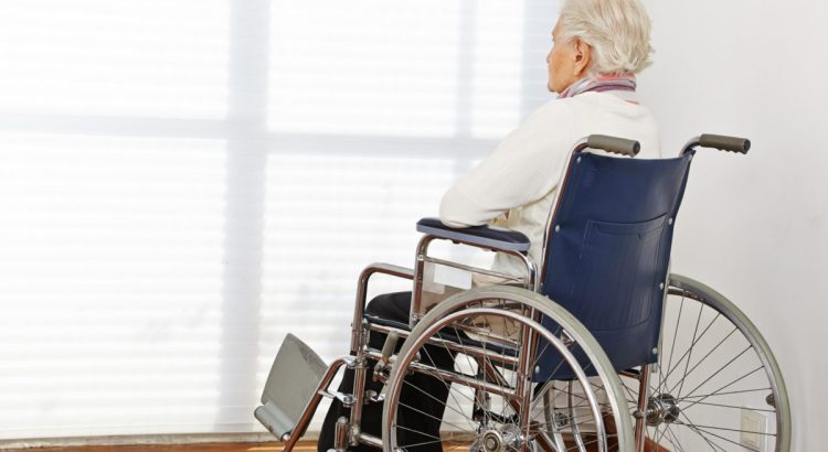 Senior citizen woman in wheelchair in a nursing home.