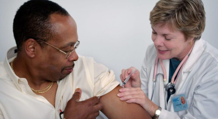 This 2006 image depicted a nurse, who was administering an intramuscular vaccination into a middle-aged man's left shoulder muscle. The nurse was using her left hand to stabilize the injection site.