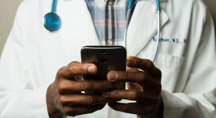 Doctor Holding Cell Phone. Cell phones and other kinds of mobile devices and communications technologies are of increasing importance in the delivery of health care. Photographer Daniel Sone.