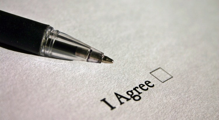 "Pen hovering over words ""I agree"" with check box next to it."