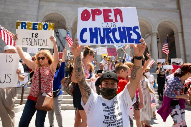 """Los Angeles, California / USA - May 1, 2020: People in front of Los Angeles' City Hall protest the state's COVID-19 stay at home orders in a """"Fully Open California"""" protest."""