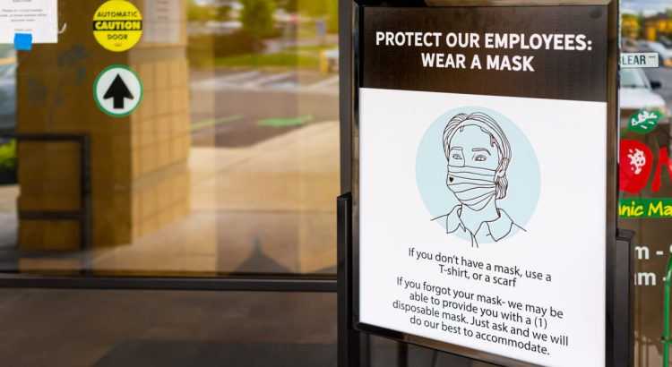 Herndon, USA - April 27, 2020: Virginia Fairfax County building exterior sign entrance to Mom's Organic Market store with request to wear face mask due to covid-19 pandemic.