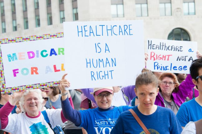 """People protesting with signs that say """"healthcare is a human right"""" and """"medicare for all."""""""
