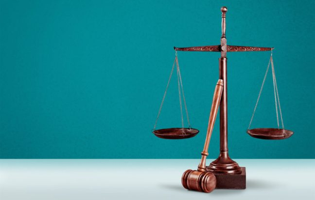 Scales of justice and gavel on table.