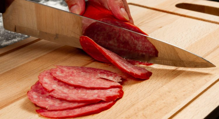 person cuts salami sausage on a wooden cutting board.