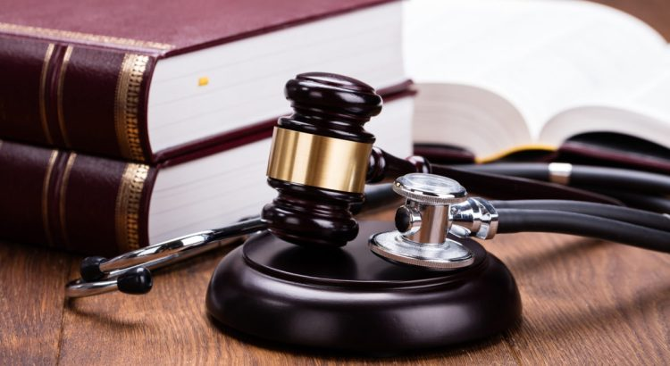 Brown Gavel With Medical Stethoscope Near Book At Wooden Desk In Courtroom.