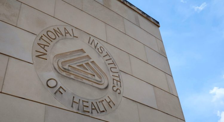 BETHESDA, MD - JUNE 29, 2019: NIH NATIONAL INSTITUTES OF HEALTH sign emblem seal on gateway center entrance building at NIH campus. The NIH is the US's medical research agency.