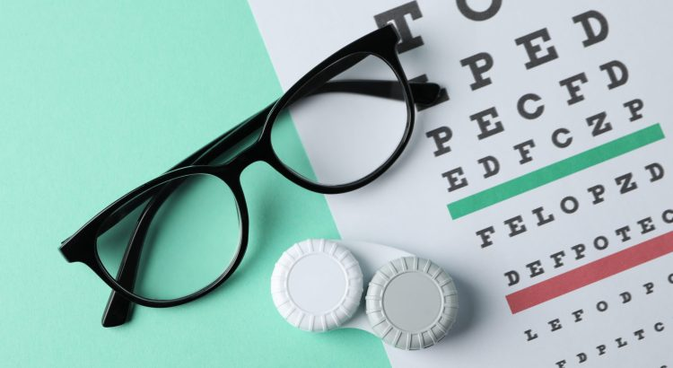 Glasses, case for contact lenses and eye test chart on mint background, top view