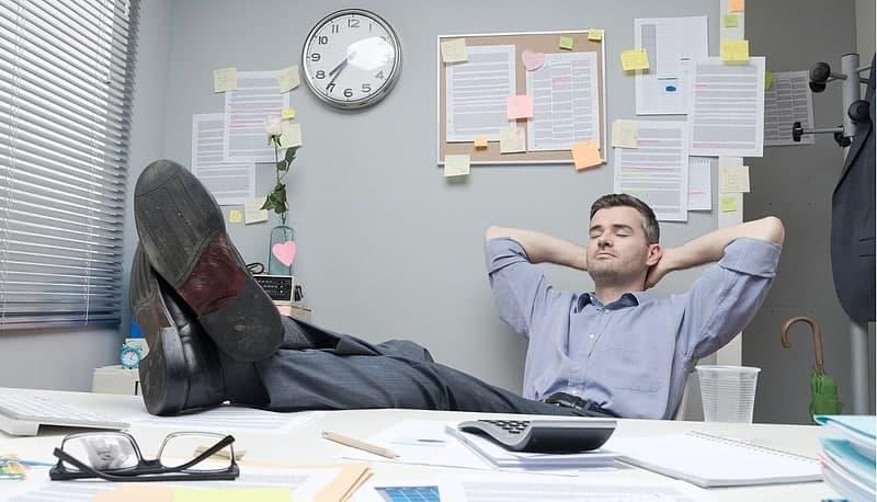 Hombre relajado en oficina con pies sobre el escritorio