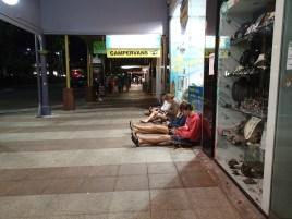 Backpacker sitzen abends vor einem Laden um das WIFI zu nutzen.
