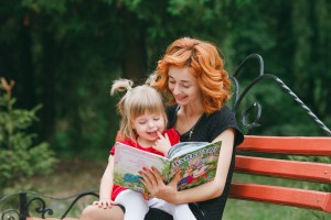 mom and little daughter reading a book on a park bench
