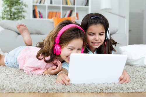 two young girls with headphones on looking at tablet