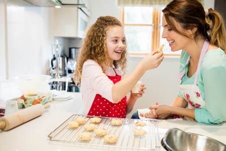 daughter feeding mother cookies in kitchen