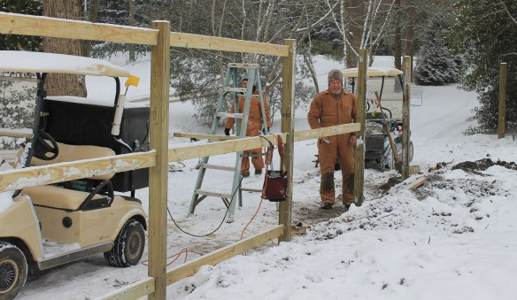 Dave and Thomas building fence in snow