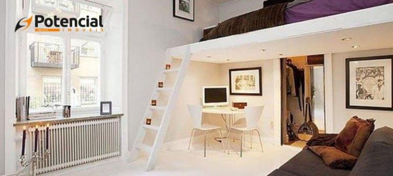 Imagem de quarto com mezanino, onde a cama está localizada. Abaixo dele, o espaço é utilizado com escrivaninha e sofá.