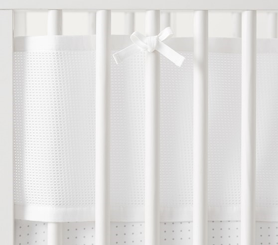 Close-up view of all-white crib liner