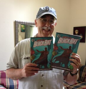 Ron Fortier holds up his latest comic book creation, Guns of the Black Bat. (Story: Ron Fortier, Aaron Shaps Art: Silvestre Szilagyi Cover: Michael Stribling)