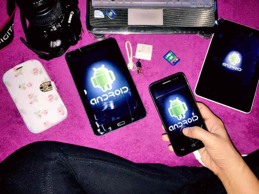 An Android UI designer sits cross-legged on the floor holding an Android smartphone. On the floor are two Android tablets of different sizes and a larger Android smartphone, in addition to a camera and laptop.