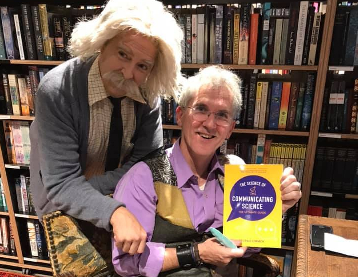Two men in front of a bookshelf, one is holding a book and the other is dressed as Albert Einstein